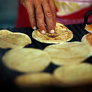 A man flips tortillas a taco at a roadside taco stand in Baja, Mexico.