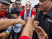 April 6, 2014 - Bangkok, Bangkok, Thailand - <br /> <br /> Red Shirts Rally in Bangkok Suburbs<br /> <br /> NATTAWUT SAIKUA, a Red Shirt core leader, is hugged by a Red Shirt as he walks through the crowd at a Red Shirt rally in a Bangkok suburb Sunday. The woman hugged him as he passed a cardboard cutout of Prime Minister Yingluck Shinawatra (left). Red Shirts and supporters of the government of Yingluck Shinawatra, the Prime Minister of Thailand, gathered in a suburb of Bangkok this weekend to show support for the government. The Thai government is dealing with ongoing protests led by anti-government activists. Legal challenges filed by critics of the government could bring the government down as soon as the end of April. The Red Shirt rally this weekend was to show support for the government, which public opinion polls show still has the support of most of the electorate. <br /> ©Exclusivepix