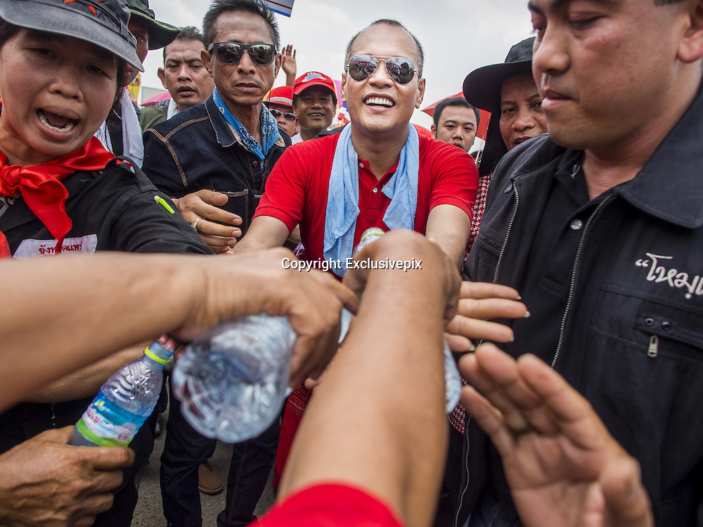 April 6, 2014 - Bangkok, Bangkok, Thailand - <br /> <br /> Red Shirts Rally in Bangkok Suburbs<br /> <br /> NATTAWUT SAIKUA, a Red Shirt core leader, is hugged by a Red Shirt as he walks through the crowd at a Red Shirt rally in a Bangkok suburb Sunday. The woman hugged him as he passed a cardboard cutout of Prime Minister Yingluck Shinawatra (left). Red Shirts and supporters of the government of Yingluck Shinawatra, the Prime Minister of Thailand, gathered in a suburb of Bangkok this weekend to show support for the government. The Thai government is dealing with ongoing protests led by anti-government activists. Legal challenges filed by critics of the government could bring the government down as soon as the end of April. The Red Shirt rally this weekend was to show support for the government, which public opinion polls show still has the support of most of the electorate. <br /> &copy;Exclusivepix