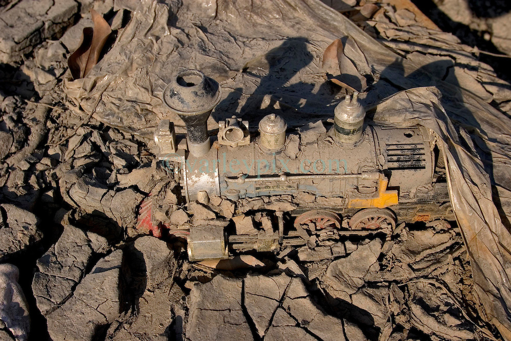 30 Sept, 2005. New Orleans, Louisiana. Lower 9th ward. Hurricane Katrina aftermath.<br /> The remnants of the lives of ordinary folks, now covered in mud as the flood waters remain. A child's toy train lies covered in mud.<br /> Photo; ©Charlie Varley/varleypix.com