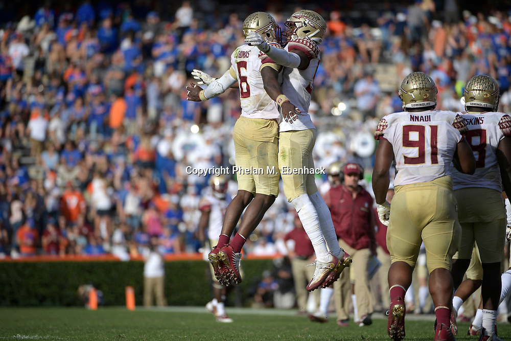 Florida State linebacker Matthew Thomas (6) is congratulated by defensive end Brian Burns after Thomas intercepted a pass during the second half of an NCAA college football game against Florida Saturday, Nov. 25, 2017, in Gainesville, Fla. FSU won 38-22. (Photo by Phelan M. Ebenhack)