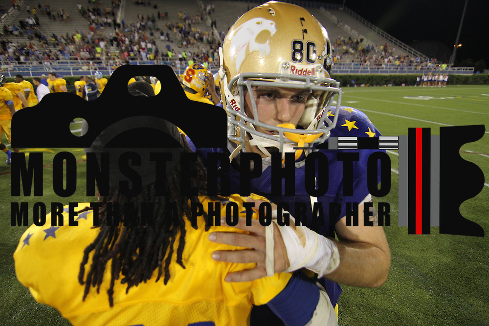 Gold Donovan Cain (21) of Dover High School hugs Blue James Rendle (80) of Saint Elizabeth High School after the playing of the 58th Annual DFRC Blue-Gold All?Star Football game Saturday, June. 22, 2013, at Delaware Stadium in Newark DE. &nbsp;&nbsp;<br />