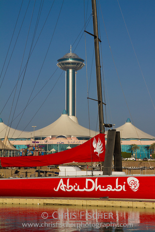 "View of Marina Mall and Marina Mall Tower from Abu Dhabi Marina & Yacht Club. Red sailboat named ""Abu Dhabi"" in foreground."