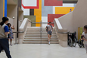 A man hitches his shorts as he descends steps with a background of geometric lines, right-angles and rectangles, on 4th August 2019, at Tate Britain, Millbank, London, England
