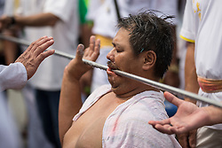 © Licensed to London News Pictures. 18/10/2015 Batu Gajah, Perak, Malaysia. A devotee with a metal pole speared through his mouth prepares for its removal at Sam Wong Kong temple during the Nine Emperor Gods Festival celebration in Batu Gajah, Malaysia, Sunday, Oct. 18, 2015. Photo credit : Sang Tan/LNP