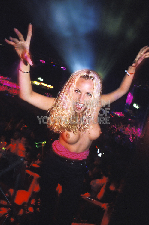 Topless blonde woman in club, posing for camera, Clubbing, UK 1990's,