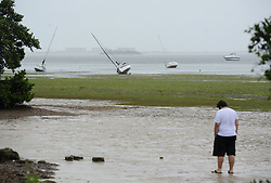 September 10, 2017 - Crystal Beach, Florida, U.S. - An unidentified individual is stands along the exposed sea floor of the Gulf of Mexico as grounded sailboats are seen in the distance Sunday. Westerly winds pushed the water from the shoreline as Hurricane Irma approached Tampa Bay. (Credit Image: © Chris Urso/Tampa Bay Times via ZUMA Wire)