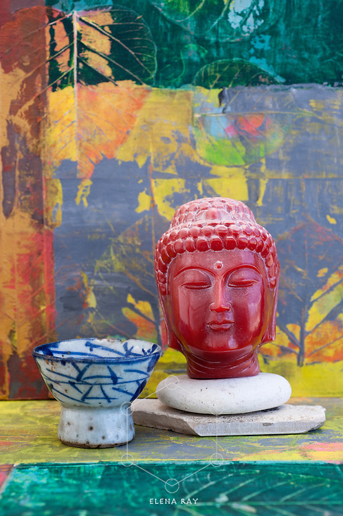 Antique buddha head and wabi-sabi saki cup.