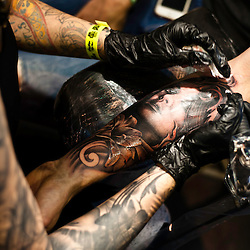 Manchester, UK - 4 August 2012: a new tattoo is created on the arm of a visitor during the Manchester Tattoo Show, one of the most popular conventions of the UK tattoo community.