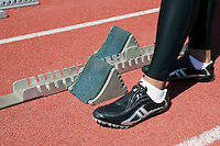 Male sprinter by track starting block