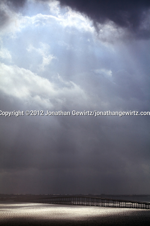 A dramatic sky full of clouds, rain and sun appears over the William Powell Bridge, part of the Rickenbacker Causeway that links Miami to the islands of Virginia Key and Key Biscayne, Florida. WATERMARKS WILL NOT APPEAR ON PRINTS OR LICENSED IMAGES.