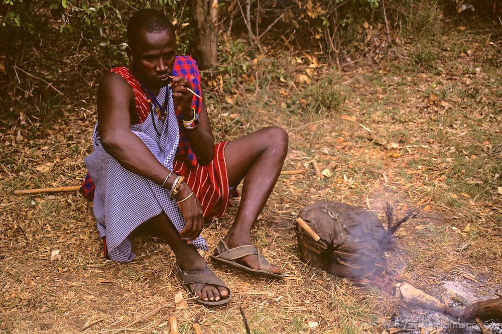 Africa, Kenya, Maasai Mara. A Maasai man sits cleaning his teeth at Olanana in the Maasai Mara.