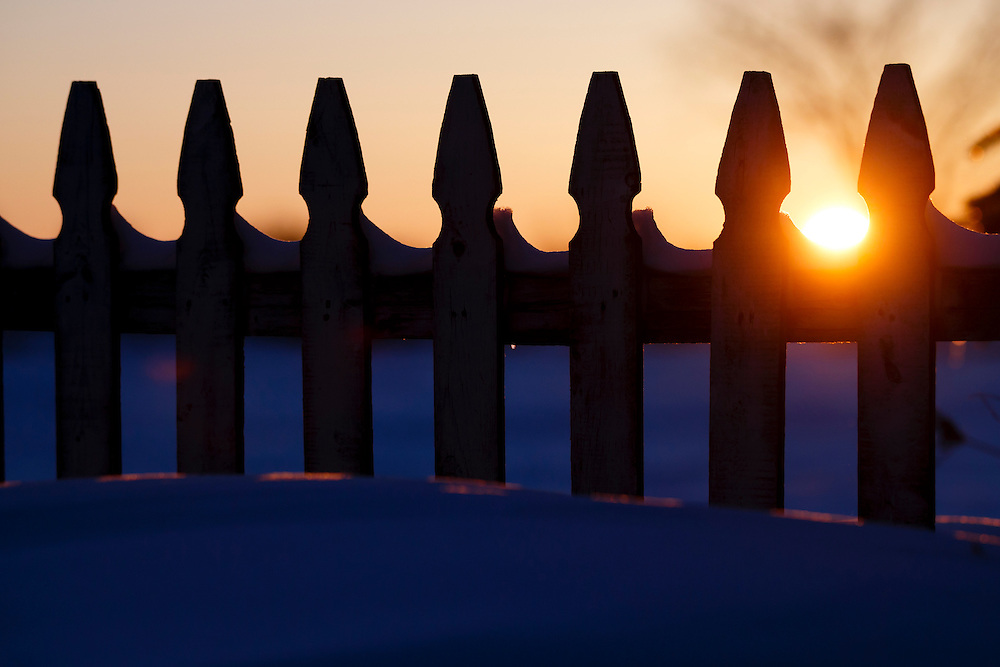 Picket fence in the winter with snow and setting sun in Martin, Ohio. Monday, Feb. 2, 2015. (Rick Osentoski)