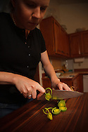 USA, Oregon, Eugene, young woman chopping a leek for dinner. MR
