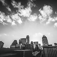 Austin Texas downtown buildings black and white photography with a partially cloudy sky at dusk. Austin, TX is a major city in the Southwestern United States of America. Picture was taken in 2016.