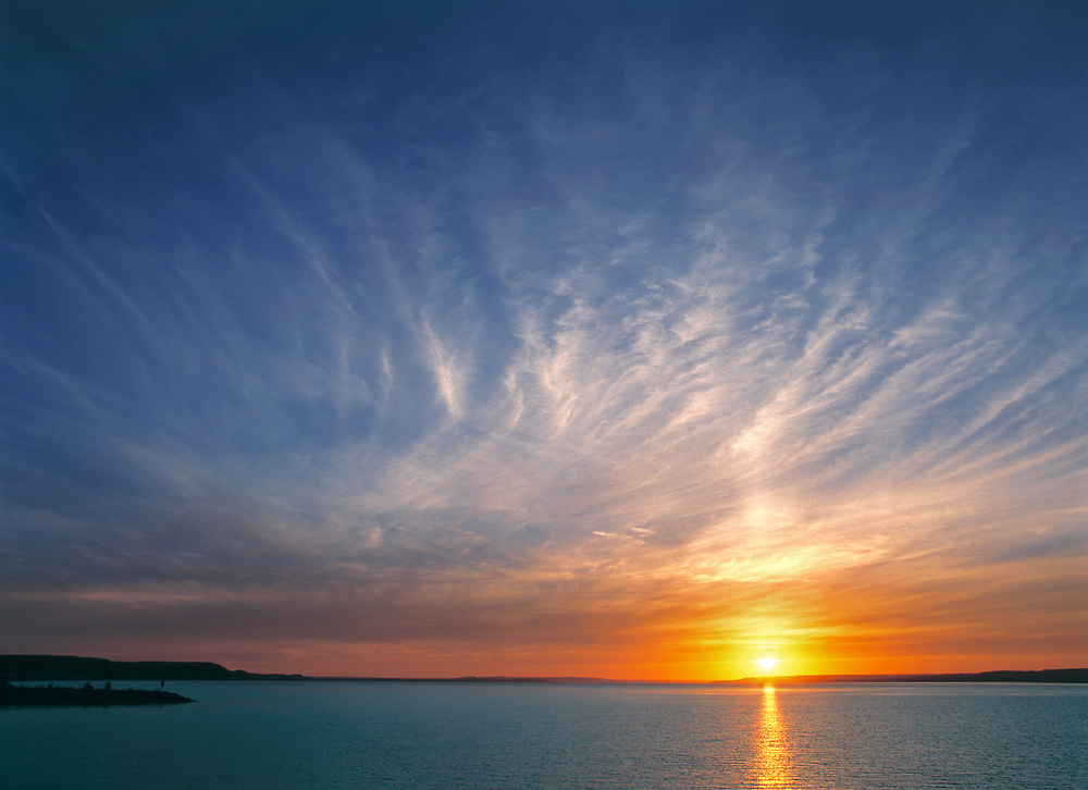 Cirrus clouds take on the colors of the sun setting over Lake Sakakawea, in North Dakota.