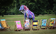 Portuguese Lusitano called Tetua age 13 painted stands behind Ronnie Wood&rsquo;s Pegasus  for the launch of Deckchair Dreams 2013, a public art initiative by the Royal Parks Foundation, in partnership with Bloomberg. Wood&rsquo;s limited-edition deckchair featuring a multi-coloured, winged horse rearing up on its hind legs.<br /> Photo By Ki Price July 4th 2013.