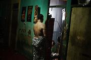 JAKARTA, INDONESIA, MARCH 2013: Saturday night - 10.30pm. Mami Joyce starts to wake the girls up for the night shift.