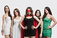 Young woman in superhero costume standing together with friends over gray background