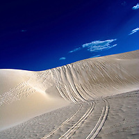 Car tracks in the desert Lancelin dunes in Australia under blue summer sky