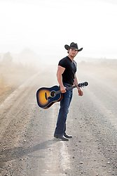 cowboy on a dusty dirt road with a guitar