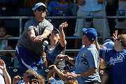 A Kansas City Royals fan is unable to catch a foul ball during a baseball game against the Cleveland Indians at Kauffman Stadium in Kansas City, Mo., Sunday, July 27, 2014.  (AP Photo/Colin E. Braley)