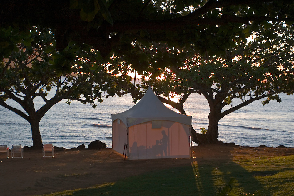 A couple on their honeymoon enjoy a dinner in the gardens of Princeville Resort at sunset.<br /> Una pareja en luna de miel disfruta de una cena al atardecer en una haima con servicio privado en la playa del hotel Princeville Resort en Kauai (Hawai).