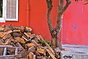 a pile of fire wood stacked outside against a red wall