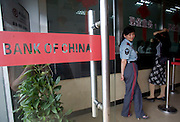 A female security guard keeps watch over a Bank of China branch office in the small town of Longnan, China.