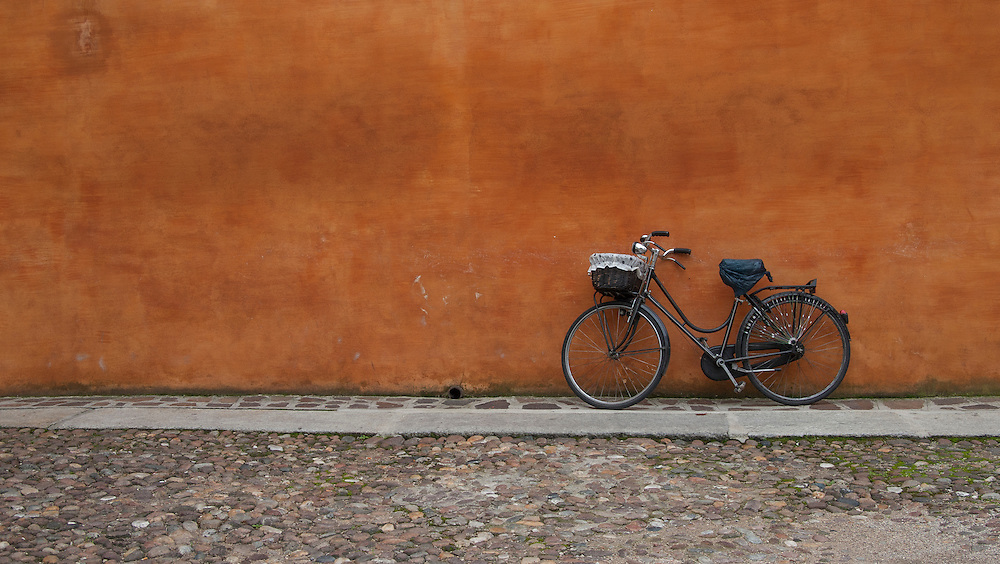 Old bike against a wall, Mantova Italy. A series of captures from a personal trip to the cities of Milan and Mantua, featuring explorations of Renaissance architecture and the vibrant life of Italian streets.