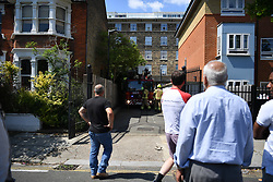 © Licensed to London News Pictures. 16/07/2019. London, UK. Tight access made reaching the fire challenging. Multiple fire engines respond to a fire in a residential block on Bromyard Avenue, in Acton, West London. A black plume of smoke was visible for miles as the penthouse apartment burned. Police helicopters, LBF drones, and paramedics were on the scene in minutes. It is not known at this stage if there were any casualties.  Photo credit: Guilhem Baker/LNP