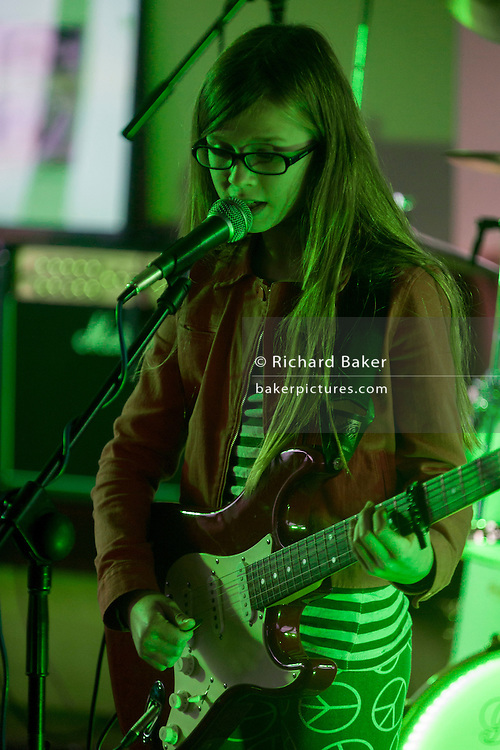 Young girl sings and plays guitar at a local music showcase in south London.