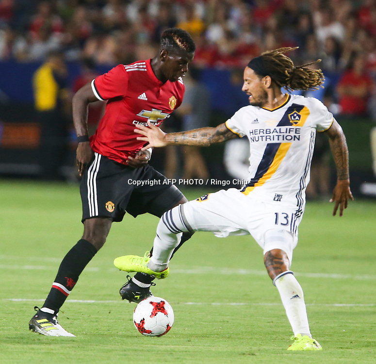 Manchester United Paul Pogba, left, and Los Angeles Galaxy Jermaine Jones battle for the ball during the second half of a national friendly soccer game at StubHub Center on July 15, 2017 in Carson, California. The Manchester United won 5-2. AFP PHOTO / Ringo Chiu