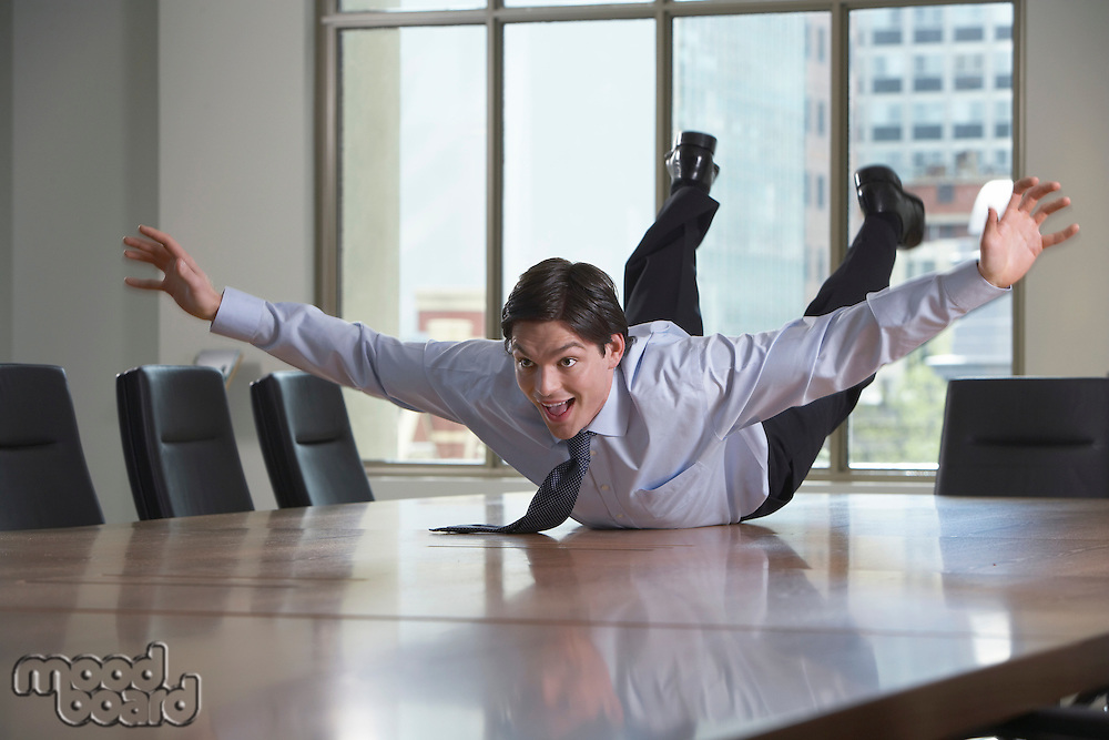 Businessman sliding on stomach on conference room table