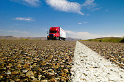 A red truck drives along an Arizona highway with a close up of the road surface. Missoula Photographer