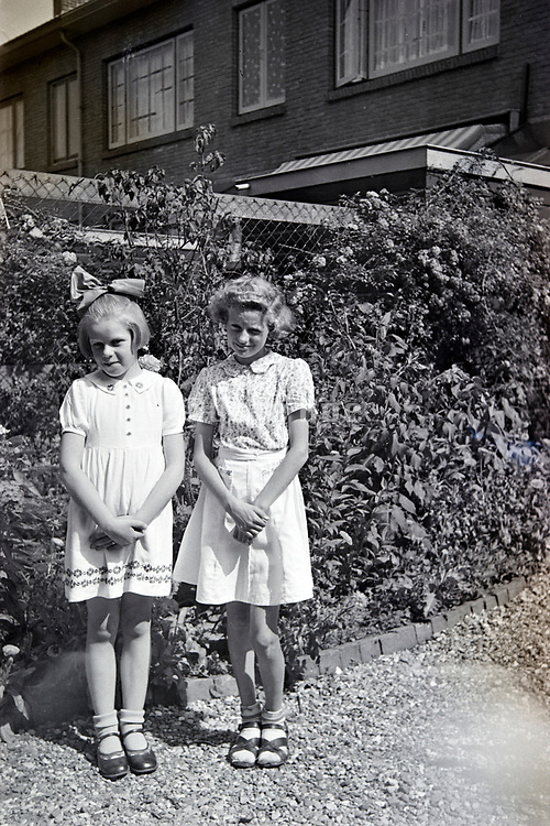 two a little shy young girls posing in the backyard 1950s Netherlands