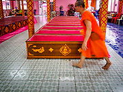 "29 MARCH 2017 - BANG KRUAI, NONTHABURI, THAILAND: A Buddhist monk walks past a row of coffins after a ""Resurrection Ceremony"" at Wat Ta Kien (also spelled Wat Tahkian), a Buddhist temple in the suburbs of Bangkok. People go to the temple to participate in a ""Resurrection Ceremony."" Groups of people meet and pray with the temple's Buddhist monks. Then they lie in coffins, the monks pull a pink sheet over them, symbolizing their ritualistic death. The sheet is then pulled back, and people sit up in the coffin, symbolizing their ritualist rebirth. The ceremony is supposed to expunge bad karma and bad luck from a person's life and also get people used to the idea of the inevitability of death. Most times, one person lays in one coffin, but there is family sized coffin that can accommodate up to six people. The temple has been doing the resurrection ceremonies for about nine years.          PHOTO BY JACK KURTZ"