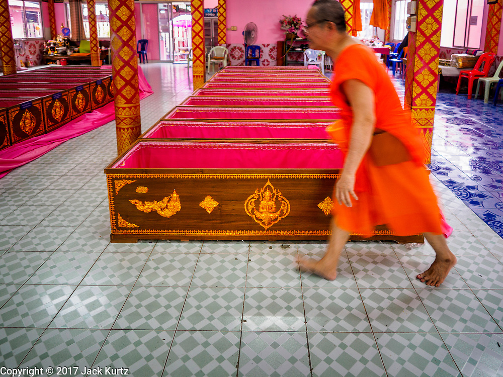 """29 MARCH 2017 - BANG KRUAI, NONTHABURI, THAILAND: A Buddhist monk walks past a row of coffins after a """"Resurrection Ceremony"""" at Wat Ta Kien (also spelled Wat Tahkian), a Buddhist temple in the suburbs of Bangkok. People go to the temple to participate in a """"Resurrection Ceremony."""" Groups of people meet and pray with the temple's Buddhist monks. Then they lie in coffins, the monks pull a pink sheet over them, symbolizing their ritualistic death. The sheet is then pulled back, and people sit up in the coffin, symbolizing their ritualist rebirth. The ceremony is supposed to expunge bad karma and bad luck from a person's life and also get people used to the idea of the inevitability of death. Most times, one person lays in one coffin, but there is family sized coffin that can accommodate up to six people. The temple has been doing the resurrection ceremonies for about nine years.          PHOTO BY JACK KURTZ"""