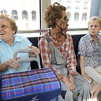 "Two women sit next to an actor dressed up like a zombie, as they travel in tram, on September 2, 2010, in the Northern Spanish city of Bilbao. Actors and dancers, dressed up like zombies, visited Bilbao to promote the musical show ""Forever, King of Pop"", based on Michael Jackson's ""Thriller"".  PHOTO/Rafa Rivas"