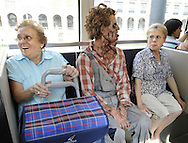 """Two women sit next to an actor dressed up like a zombie, as they travel in tram, on September 2, 2010, in the Northern Spanish city of Bilbao. Actors and dancers, dressed up like zombies, visited Bilbao to promote the musical show """"Forever, King of Pop"""", based on Michael Jackson's """"Thriller"""".  PHOTO/Rafa Rivas"""