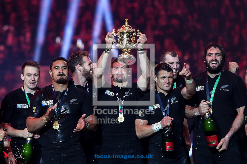 Richie McCaw of New Zealand (centre) holds the World Cup trophy aloft as Dan Carter of New Zealand (second right) celebrates after the final of the 2015 Rugby World Cup at Twickenham Stadium, Twickenham<br /> Picture by Andy Kearns/Focus Images Ltd 0781 864 4264<br /> 31/10/2015