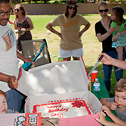 birthday party in the park for three year old with cake, friends and parents