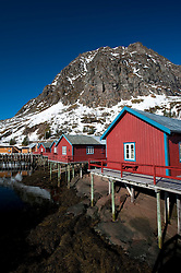 Traditional red wooden fishermen`s Rorbu huts by sea in Tind village in Lofoten Islands in Norway