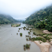 An elevated view looking down Nam Ou (River Ou) in Nong Khiaw in northern Laos. The sandy bottom of the river means that the current creates small, sandy islands and protected inlets on the river. In the distance, the regular morning mists shroud the mountainous terrain on either side of the river.