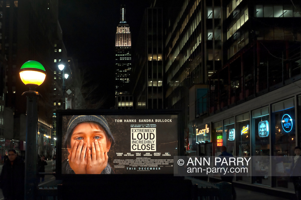 """Manhattan, NY, USA - January 9, 2012: Movie poster """"Extremely Loud & Incredibly Close"""" hangs illuminated at night over Penn Station subway entrance with Empire State Building in background. Fictional movie is set at time of 9/11 terrorist attacks on Twin Towers in NYC. Green and yellow lit globe on post is at stairwell entrance to MTA (Metropolitan Transit Authority) 34 St. Penn Station subway station."""