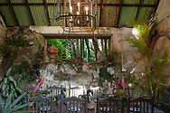 Interior of the old factory shed with table set for dinner and collected ornaments in Hunte's Gardens, Coffee Gully, St. Joseph, Barbados