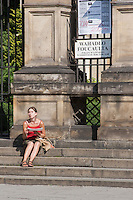 Woman sittting on the steps of St Peter and Paul church in Krakow Poland