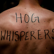 Some wrestlers sported their team names on their body with permanent marker during the 28th annual Hog Wrestling Competition at Caldron Falls Bar in Twin Bridge, Wis., on July 20, 2013. Lukas Keapproth/Press Gazette Media