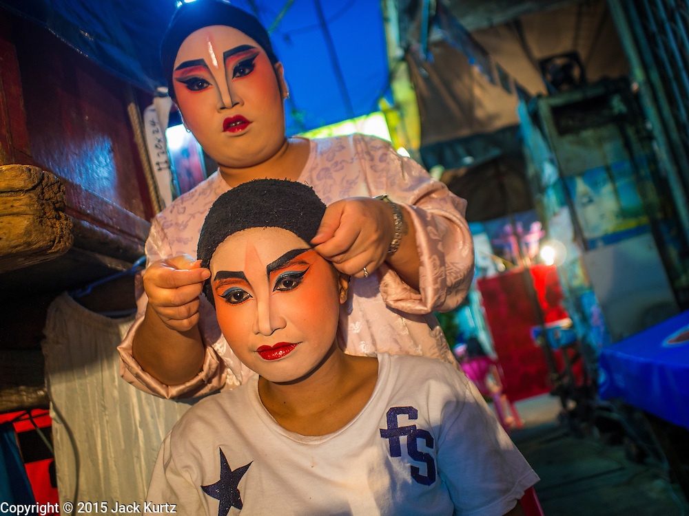 16 JANUARY 2015 - BANGKOK, THAILAND: Performers with the Sai Yong Hong Opera Troupe help each other get ready for a performance at the Chaomae Thapthim Shrine, a Chinese shrine in a working class neighborhood of Bangkok near the Chulalongkorn University campus. They don't have dressing rooms per se, instead setting up their make up tables right on the sidewalk. The troupe's nine night performance at the shrine is an annual tradition and is the start of the Lunar New Year celebrations in the neighborhood. Lunar New Year, also called Chinese New Year, is officially February 19 this year. Teochew opera is a form of Chinese opera that is popular in Thailand and Malaysia.    PHOTO BY JACK KURTZ