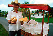 CUBA, ISLE OF YOUTH Man delivering daily allotment of bread, one loaf per person, rural village